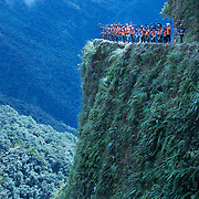 """Mountain Biking on Death Road, Bolivia...A tour group of Mountain Bikers pose for a photograph on a landmark bend of the infamous narrow dirt road, most of the road no wider than 3.2meter's, is cut into the side of the mountain with sheer drops to the left of up to 600 meter's with virtually no safety rails on the winding steep decent...The North Yugas Road is a 64 Kilometer road leading from La Paz to Corioico. It is legendary for it's extreme danger and in 1995 the Inter American Development Bank christened is as the """"world's most dangerous road"""".. The road was built in the 1930's during the Chaco War by Paraguayan prisoners to connect the Amazon rainforest region of Northern Bolivia to it's capital City La Paz. One estimate is that 200 to 300 travelers were killed yearly along the road. On 24 July 1983, a bus veered off the Yungas Road and into a canyon, killing more than 100 passengers in what is said to be Bolivia's worst road accident..A new stretch of the La Paz-Coroico highroad was opened in 2006 to bypass the notorious stretch known as death road..The danger of the road has now made it a popular tourist destination starting in the 1990's and drawing thrill-seekers and mountain bike enthusiasts who ride on the 64km mainly downhill stretch from La Cumbre, a 4,700 meter peak to Yolosa, a decent of 3600 meter's (11,800 feet). The journey includes breathtaking views of snow covered peaks and towering cliffs and starts along modern asphalted road before entering the jungle itself and the most dangerous and notorious part of the ride. The infamous narrow dirt road, most of the road no wider than 3.2meter's, is cut into the side of the mountain with sheer drops to the left of up to 600 meter's with virtually no safety rails on the winding steep decent..There are now many tour operators catering to this activity, providing information, guides, transport and equipment. Nevertheless, the Yungas Road remains dangerous. At least 13 of these cyclists died on the ride s"""
