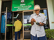 15 DECEMBER 2016 - PRACHINBURI, THAILAND:  A man leaves a government credit union after picking up his cash disbursements in Prachinburi, Thailand. The Thai government said people who earn 30,000 Baht (about $857 US) or less per year are entitled to a 3,000 Baht cash payment (about $85.7 US) and those who earn 30,000 Baht to 100,000 Baht (about $2,857 US) per year are entitled to a 1,500 Baht (about $42.8 US) cash payment. The plan is meant to help low income people, especially the rural poor. Government banks in rural areas offering the disbursement have been crowded with people seeking their payments this week.     PHOTO BY JACK KURTZ   Social Safety Net