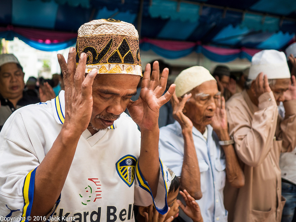 06 JULY 2016 - BANGKOK, THAILAND: Men pray during Eid services at Ton Son Mosque in the Thonburi section of Bangkok. Eid al-Fitr is also called Feast of Breaking the Fast, the Sugar Feast, Bayram (Bajram), the Sweet Festival or Hari Raya Puasa and the Lesser Eid. It is an important Muslim religious holiday that marks the end of Ramadan, the Islamic holy month of fasting. Muslims are not allowed to fast on Eid. The holiday celebrates the conclusion of the 29 or 30 days of dawn-to-sunset fasting Muslims do during the month of Ramadan. Islam is the second largest religion in Thailand. Government sources say about 5% of Thais are Muslim, many in the Muslim community say the number is closer to 10%.        PHOTO BY JACK KURTZ