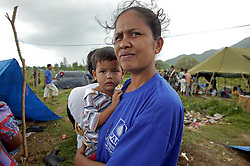 Seleena with her daughter standing still bewildered by the tragic events of Dec 26th in the army camp where they have taken shelter and from where basic services are provided. The Indonesian army provided space in one of their camps for 2,500 villagers and army staff from the west coast who had trekked across the hills to find food and shelter. Banda Aceh