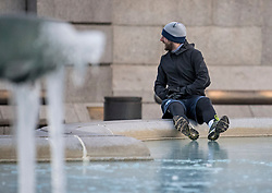 © Licensed to London News Pictures. 13/02/2021. London, UK. A man tests the thickness of the ice at The fountains at Trafalgar Square in central London, which remain frozen over following another night of sub zero temperatures in the capital. Photo credit: Ben Cawthra/LNP