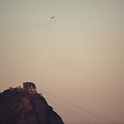 A airline jet flies past the summit of Suger Loaf Mountain, one of the iconic locations with breathtaking views of Rio de Janeiro, Brazil. 22nd July 2010. Photo Tim Clayton..