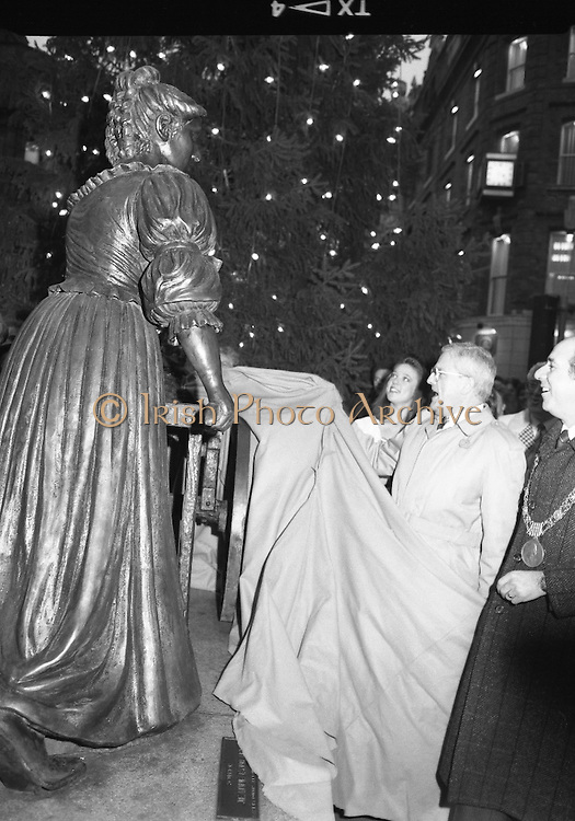 """Molly Malone Statue Unveiled. (R93)..1988..20.12.1988..12.20.1988..20th December 1988..""""Dublin's Fair City"""" received a millenniun gift to commemorate her most famous daughter, Molly Malone, when Jurys Hotel Group plc presented a specially commissioned sculpture to the people of Dublin. The sculpture was formally handed over by Michael McCarthy, MD,Jurys Hotel Group, to the Lord Mayor of Dublin, Councillor Ben Briscoe, TD, in an unveiling ceremony today at the corner of Grafton Street, Suffolk Street and Nassau Street..Molly Malone was created and fashioned in her traditional 17th century dress by Dublin born artist, Jeanne Rynhart, who was selected from a number of entries for the statue design, by the Dublin Millennium Board...Image shows Lord Mayor, Ben Briscoe and Jurys MD, Michael McCarthy officially unveiling the statue of Molly Malone."""