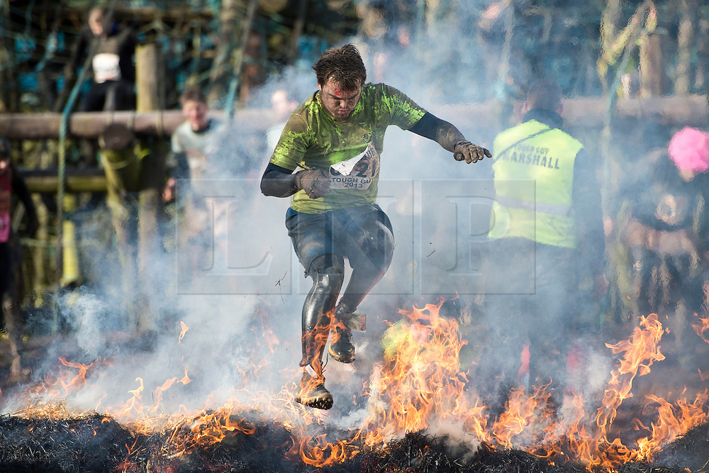 """©  London News Pictures. 27/01/2013.  A Competitor leaping over flames as he is pushed to the limits  in the 2013 Tough Guy Challenge on January 27, 2013 in Wolverhampton, England. The event has been widely described as """"the toughest race in the world"""", with over one-third of the starters failing to finish in a typical year. Photo credit: Ben Cawthra"""