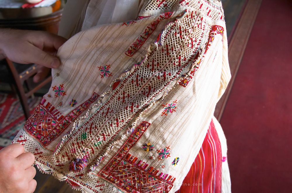 Detail of woman's clothing, finely embroidered cloth in many colours. Tradita traditional restaurant, Shkodra. Albania, Balkan, Europe.