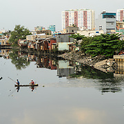 Two men in a small sampan use a net on a pole to fish on the Saigon River in Ho Chi Minh City, Vietnam.