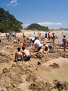 People swarm to enjoy the naturally, geothermally warm sand and water under the beach at Hot Water Beach on the Coromandel Peninsula, New Zealand