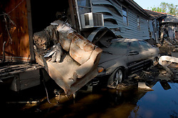 30 Sept, 2005.  New Orleans, Louisiana. Lower 9th ward. Hurricane Katrina aftermath. <br /> The remnants of the lives of ordinary folks, now covered in mud as the flood waters remain. A child's teddy bear, covered in mud rests on a couch in what remains of a house that rests on a car.<br /> Photo; ©Charlie Varley/varleypix.com