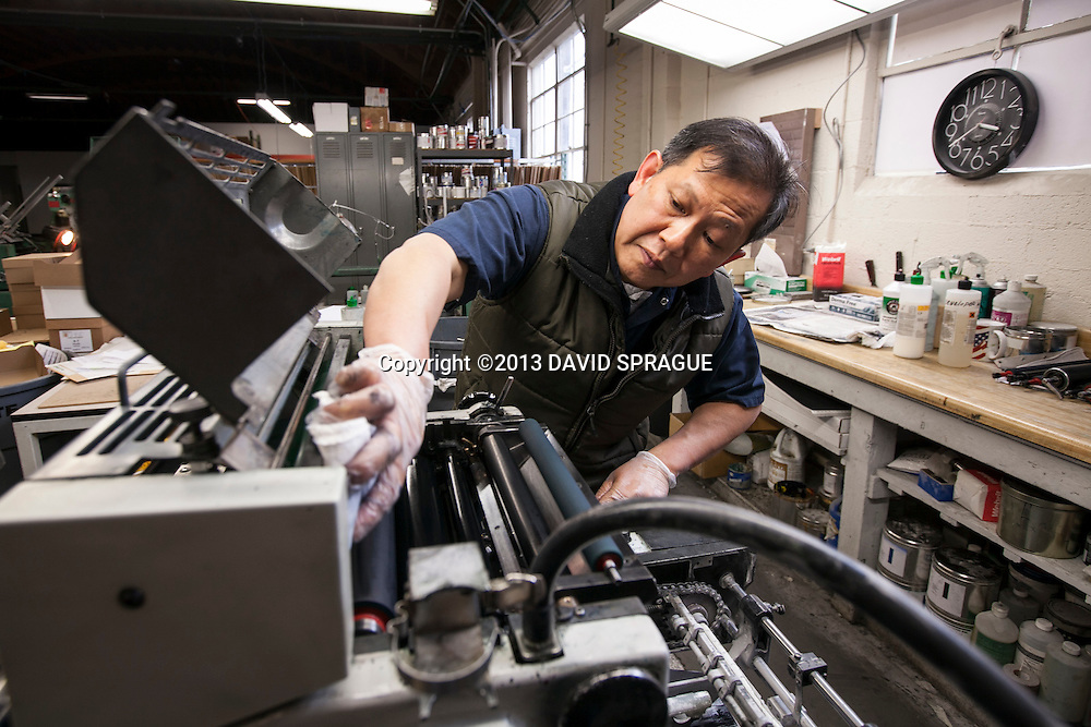 Paul Truong cleans a small offset press at Harman Press, CA. Shot Feb. 19th,  2013 Photo by David Sprague ©2013