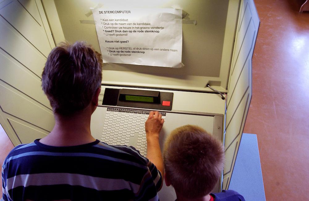 Nederland, Maarssen, 10 juni 2004.Europese Verkiezingen..Stembureau, stemmen, stemhokje.Moeder en kind brengen stem uit...Foto (c) Michiel Wijnbergh..