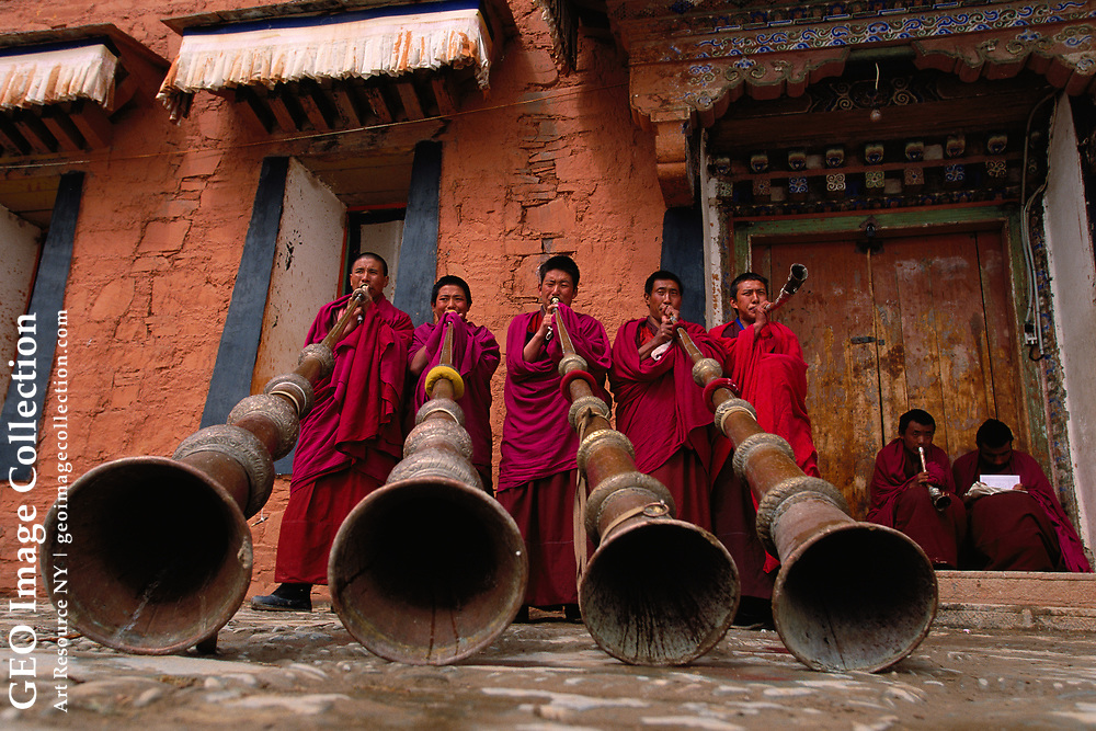 Labrang Monastery, novice monks (trapa), practice blowing the dungchen, traditional 13-foot horns, that will be used in Buddhist ceremonies and call to prayer. The sound can be compared to the singing of elephants. Gansu, China