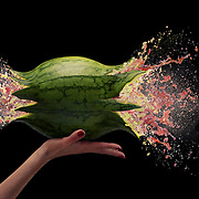 Watermelon held in a hand with a bullet going through it creating an explosion Ray Massey is an established, award winning, UK professional  photographer, shooting creative advertising and editorial images from his stunning studio in a converted church in Camden Town, London NW1. Ray Massey specialises in drinks and liquids, still life and hands, product, gymnastics, special effects (sfx) and location photography. He is particularly known for dynamic high speed action shots of pours, bubbles, splashes and explosions in beers, champagnes, sodas, cocktails and beverages of all descriptions, as well as perfumes, paint, ink, water – even ice! Ray Massey works throughout the world with advertising agencies, designers, design groups, PR companies and directly with clients. He regularly manages the entire creative process, including post-production composition, manipulation and retouching, working with his team of retouchers to produce final images ready for publication.