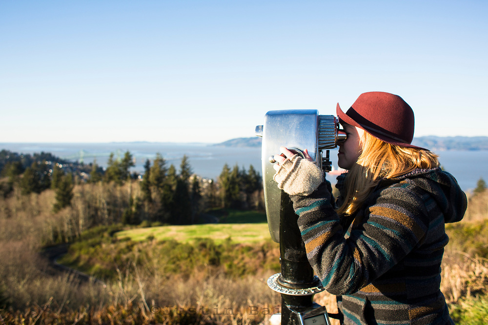 Young woman looking through an old fashioned vew finder in Astoria, OR.