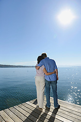 Mature couple standing and embracing each other on boardwalk, Bavaria, Germany