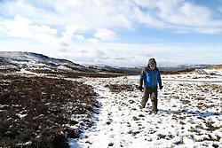 © Licensed to London News Pictures. 02/03/2016. Ilkley, UK. A man walks through the snow atop a cold Ilkley Moor after heavy snow fall in Yorkshire this morning.  Forecaster are predicting more snowfall and strong winds as Storm Jake moves in. Photo credit : Ian Hinchliffe/LNP