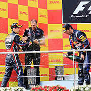 Red Bull Formula One driver Sebastian Vettel of Germany (L) celebrates with the trophy on the podium as team mate Mark Webber of Australia (R) watch, after he won the Turkish F1 Grand Prix at the Istanbul Park circuit in Istanbul May 8, 2011. Photo by TURKPIX