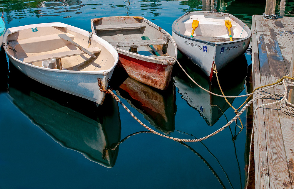 Reflections of three dinghies and their painters.