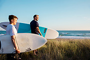 Father and son holding their surfboards and watching the surf and breaking waves at St Ouen's Bay, Jersey, Channel Islands at sunset