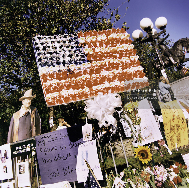 "Patriotic Americana - After 9/11.Collection of iconic imagery, Union Square NYC.In the week after the September 11th attacks, America sought to express their anger and patriotic unity. Messages of support, grief and unwelcome dissent are displayed around Union Square, accompanied by a cut-out of John Wayne. New York City. ""The voice of freedom will not be silenced."" - From CNN"