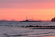 The sun sets behind the White Rock Pier and Vancouver Island's mountains - from White Rock, British Columbia, Canada. Air pollution or smoke from a recent fire in Squamish account for the atmospheric conditions.