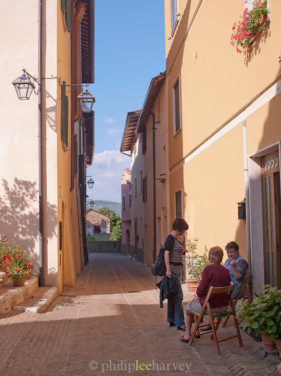Woman chat in the small, quiet streets in Solomeo, Umbria, Italy