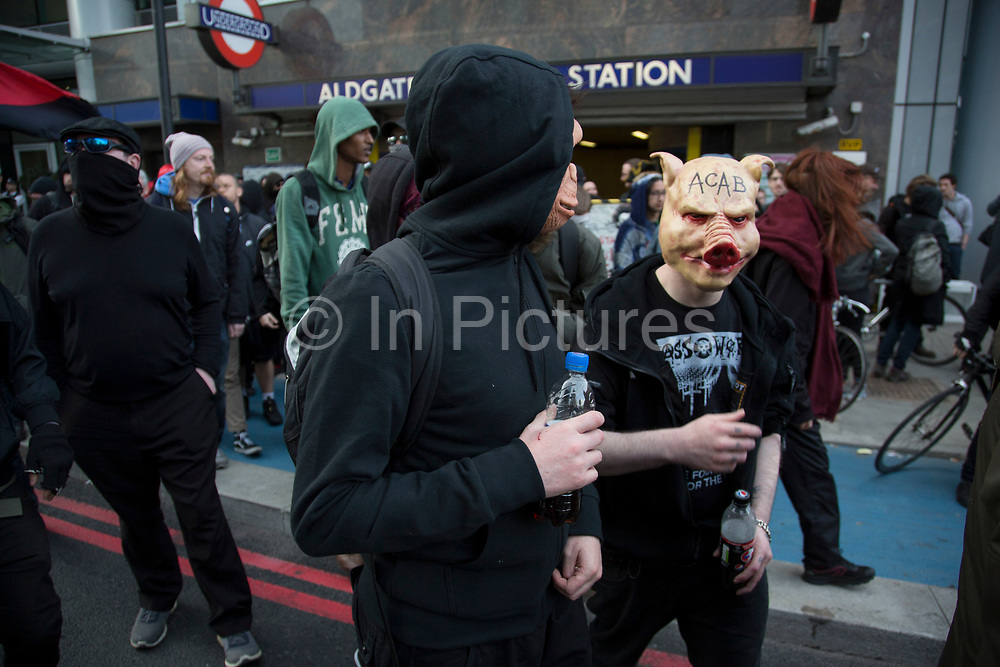 Anarchists gather as a black bloc for the Fuck Parade to party and protest at the class and wealth divide between rich and poor and the gentrification of London, the demonstration was organised by anarchist group Class War on May 1st 2016 in London, United Kingdom. The parade is now part of the May Day activism calendar as dissatisfaction about the establishment, the police and the inadequacy of the press is highlighted. Protester wearing a pig face head emblazoned with the letters ACAB meaning All Coppers Are Bastards amonst coloured smoke from a smoke bomb.