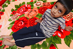 Portrait of young boy sitting on a rug,