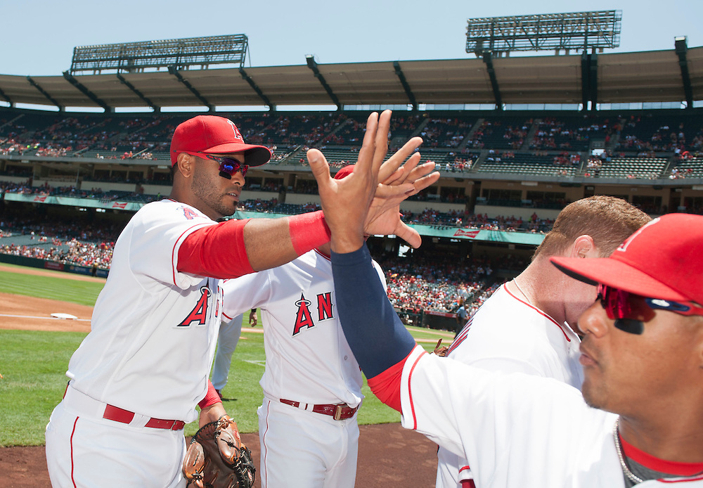 The Angels' Gregorio Petit high-fives Yunel Escobar after making a nice catch to start a double play to end the top the first inning against the Chicago White Sox at Angel Stadium on Sunday.<br /> <br /> ///ADDITIONAL INFO:   <br /> <br /> angels.0718.kjs  ---  Photo by KEVIN SULLIVAN / Orange County Register  -- 7/17/16<br /> <br /> The Los Angeles Angels take on the Chicago White Sox at Angel Stadium.