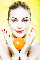 beautiful caucasian woman portrait holding an orange studio on yellow background