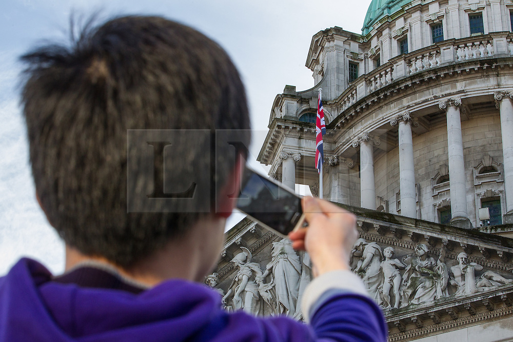 © Licensed to London News Pictures . 09/01/2013 . Belfast , UK . A tourist stops to take a photograph of the flag . The Union Jack flag is flown at Belfast City Hall today (9th January 2013) to mark the Duchess of Cambridge's 31st birthday . On 3rd December , councillors voted to limit the number of days the flag would be flown , sparking weeks of violence . Photo credit : Joel Goodman/LNP