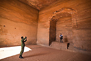 A tourist has her picture taken inside the cavernous interior of The Monastery (Al Deir) in Petra, Jordan.