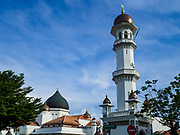 """22 AUGUST 2018 - GEORGE TOWN, PENANG, MALAYSIA: The main minaret of Kapitan Keling Mosque in George Town. It is the oldest mosque in George Town. Eid al-Adha, """"Feast of the Sacrifice"""" is the second of two Islamic holidays celebrated worldwide each year. It honors the willingness of Ibrahim (Abraham) to sacrifice his son as an act of obedience to God's command.     PHOTO BY JACK KURTZ"""