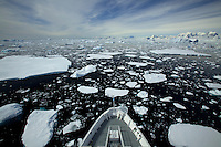 National Geographic Endeavor cruises through sea ice and past icebergs in the Grandidier Channel, Antarctica.