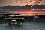Kilve beach close to sunset, with the sun poking through the clouds over the Bristol Channel and the picnic table in the foreground.