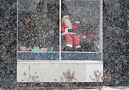Middletown, NY - A mechanical Santa waves from the window of a store as snow falls during a winter storm on Dec. 19, 2008.
