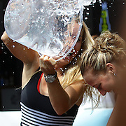 Caroline Wozniack, (left), empties the remains of her ice bucket on fellow player Petra Kvitova, (right), after Tournament Director Anne Worcester took the ALS Ice Bucket Challenge with the help of Tennis players Simona Halep, Caroline Wozniack and Petra Kvitova, during the Connecticut Open at the Connecticut Tennis Center at Yale, New Haven, Connecticut, USA. 17th August 2014. Photo Tim Clayton