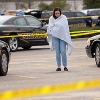 A woman tries to stay warm wrapped in a blanket within the crime scene area cordoned off at the scene of a shooting where two people died Friday afternoon near the Monkey Junction Wal-Mart in Wilmington, N.C. on Friday, February 6, 2015. StarNews Photo by Mike Spencer