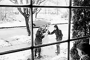 0003-041. Winter Window Vista. The children of photographer Stuart Fresk are building a snowman in their front yard. Ca. 1960. The location is 1609 23rd Avenue, Longview, Washington.