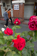 Seen through the Labour Party symbol red roses, voters arrive at the polling station on the morning of the UK 2017 general elections outside the polling station at St. Saviours Parish Hall in Herne Hill, Lambeth, on 8th June 2017, in London, England.