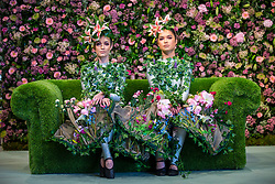 © Licensed to London News Pictures. 25/04/2018. Harrogate UK. Dancer Alison Parsons (left) & Georgia Paton Durrant (right) wear flower dresses in living room of the Green House display at this years Harrogate Flower Show in which starts tomorrow.  The GREENhouse has been designed to blur the lines between house and garden, creating a home infused with nature complete with living wallpaper,cascading flower shower, an aromatic bed of herbs and even a vege-table. Photo credit: Andrew McCaren/LNP