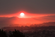 Looking west across San Francisco Bay from the East Bay hills over Point Richmond as the sun sets through wildfire smoke over the Marin Headlands, south of the Sonoma and Napa wildfires. Air quality on this day was rated as bad in San Francisco as in Beijing China. 12th October, 2017.