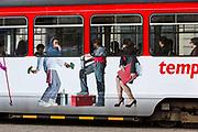 Side view of a De Lijn tram decorated with artwork of passengers legs below the window in Ghent, Belgium.