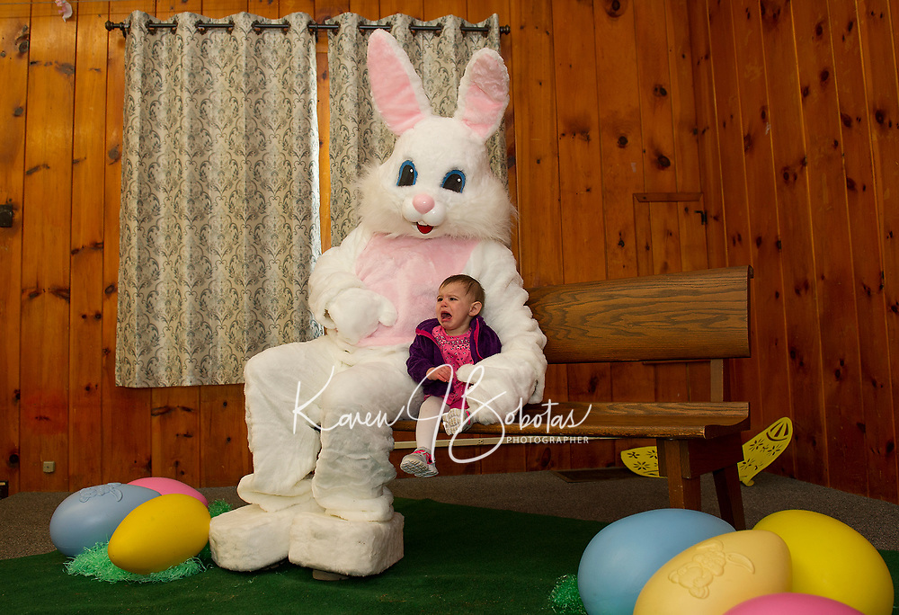 Ella Mahan isn't happy as she sits with the Easter bunny inside the Leavitt Park Clubhouse during Laconia Parks and Recreation Easter festivities on Sunday afternoon.  (Karen Bobotas/for the Laconia Daily Sun)