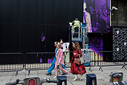 Stylish people walk beneath a workman with an events company who is removing sticky banners from the side of a venue on the Strand where shows have been held during London Fashion Show, on 17th February 2020, in London, England.