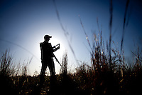 SILHOUETTE OF A TURKEY HUNTER CALLING WITH A BOX CALL