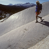 A hiker descends glacier-polished granite slabs on Daff Dome near Tuolumne Meadows in Yosemite National Park, California.