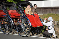 Rickshaw Passengers - Rickshaws still ply the streets of Arashiyama in the rural part of Kyoto. Nowadays the rickshaw pullers tend to be university students, working at a part-time job rather than this being a blue-collar low level job.