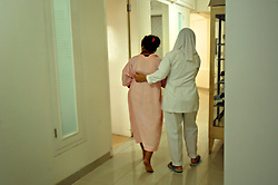 A woman is led back to her room after having an abortion at a medical clinic that secretly performs safe abortions in Jakarta, Indonesia, April 25, 2006. A woman who has an abortion can get four years in jail while the doctor who performed it can get up to 15 years. Yet 2.3 million abortions are performed in Indonesia every year, many by unskilled practitioners. Thousands of women survive but often with life-long disabilities. It is said by doctors and activists that a woman dies every hour in Indonesia due to unsafe abortions.