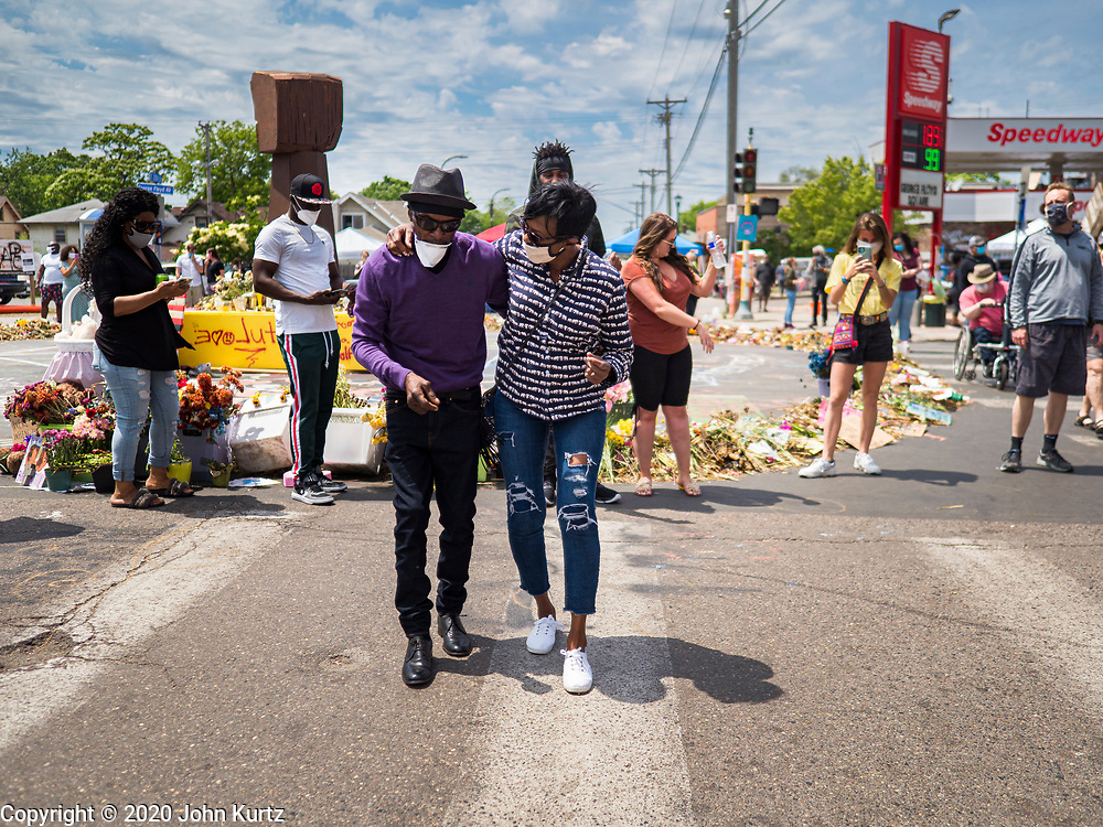 """12 JUNE 2020 - MINNEAPOLIS, MINNESOTA: A couple dances at the impromptu memorial for George Floyd at the corner of 38th Street and Chicago Ave. in Minneapolis. The intersection is informally known as """"George Floyd Square"""" and is considered a """"police free zone."""" There are memorials to honor Black people killed by police and people providing free food at the intersection. Floyd, an unarmed Black man, was killed by Minneapolis police on May 25 when an officer kneeled on his neck for 8 minutes and 46 seconds. Floyd's death sparked weeks of ongoing protests and uprisings against police violence around the world.          PHOTO BY JACK KURTZ"""