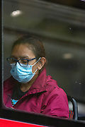 A person wearing a face protective surgical mask is seen sitting on a red bus in central London on Sunday, Aug 8, 2021. Scientists are warning the public not to be complacent, saying high levels of infection in the community are likely to lead to another spike in cases this fall. (VX Photo/ Vudi Xhymshiti)